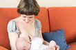 Young beautiful Mother breastfeeding her newborn baby