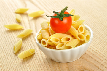 Several uncooked penne pasta and a cherry tomato in a small bowl
