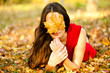 beautiful girl covers face autumn leaves