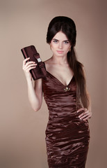 Elegant fashion brunette woman in dress with handbag