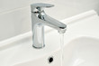 A tap on a bathroom sink against a white wall.