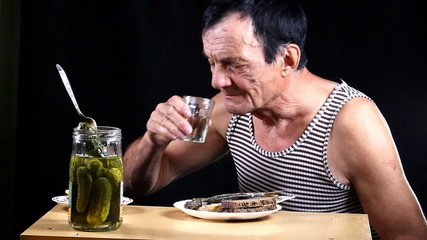 Man drinks and bites pickle