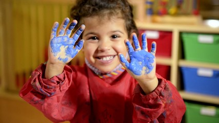Happy children having fun and painting in kindergarten