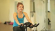 Sporty woman training on cycle in sport club