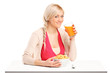 A young female drinking a juice and eating cornflakes at breakfa