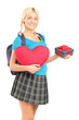 Blond beautiful student holding a red heart and a gift