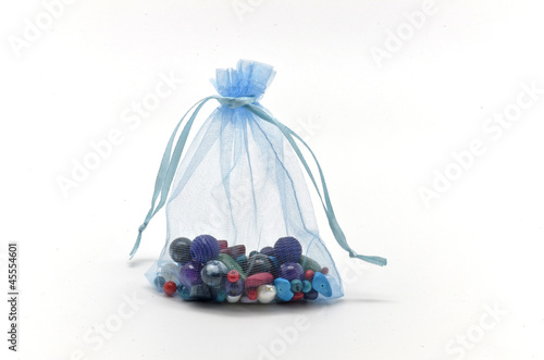 Blue cloth bag filled with glass beads for jewelry