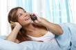 Junge hübsche Frau telefoniert im Bett