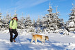 Woman hiking with dog in winter, Poland