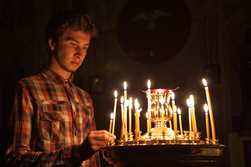 Young man lighting a candle in the church.