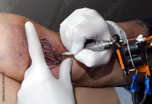 Tattoo artist makes the tattoo on arm