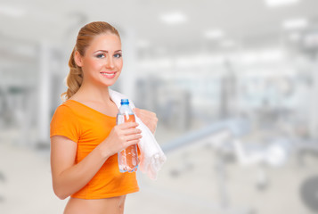 Young woman with water bottle and towel