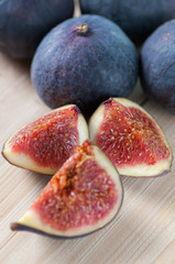 Vertical shot of ripe figs and its slices on wooden boards