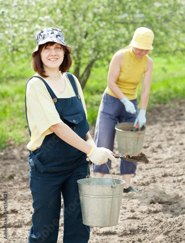 women fertilizes  soil in garden