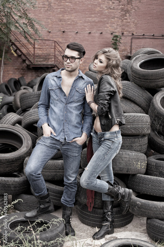 Sexy and fashionable couple wearing jeans, grungy location
