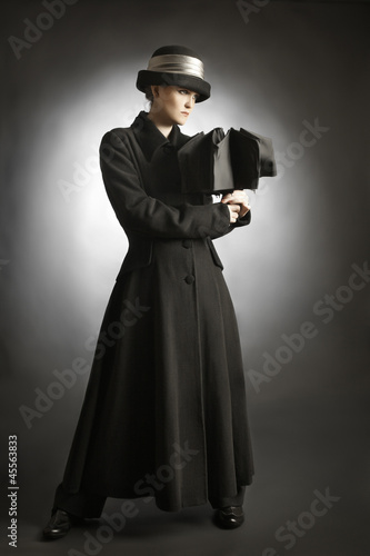 Fashion model in black coat and hat