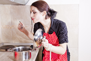 Attractive housewife tasting food