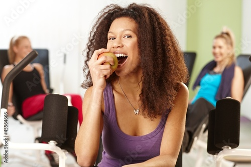 Pretty afro girl biting an apple at the gym