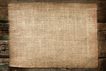 Burlap jute canvas vintage background on wooden boards