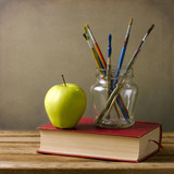 Paint brushes and books on wooden tabletop against grunge wall poster