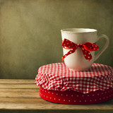 Mug with ribbon on round box on wooden tabletop. Gift concept. poster