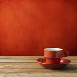 Red coffee cup on wooden deck tabletop against red grunge wall poster