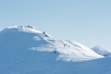 People on the snow-covered mountain peaks.