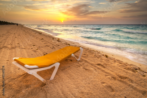 Yellow deckchair on the Caribbean Sea at sunrise