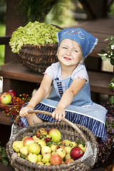 happy little girl holding a basket with pears