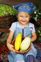 happy little girl holding а bowl with vegetables