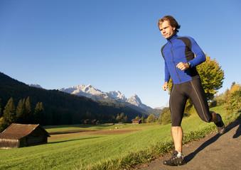 Jogger in der Natur mit Bergen im Hintergrund