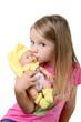 Bambina seduta che bacia un bambolotto