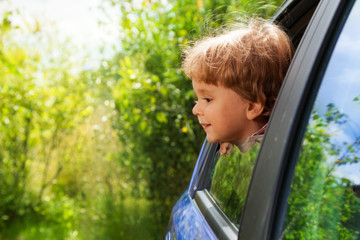 curious kid looking outside of car window