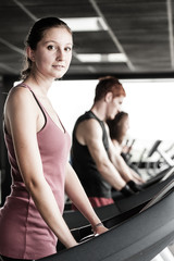 Running on treadmill in gym or fitness club - group of women and