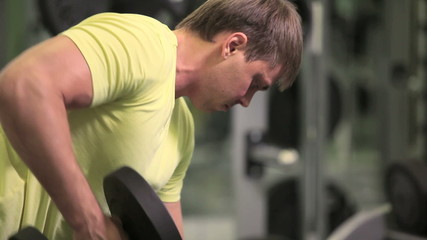 Muscular man lifting dumbbell in sport club