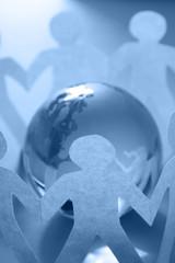 Closeup of paper people around a glass globe