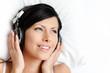 Woman in underwear listens to music through the headphones