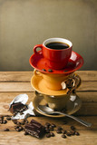 Colorful cups with coffee on wooden tabletop against grunge wall poster