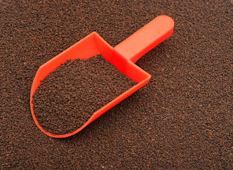 plastic measuring spoon with dried black tea