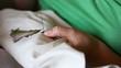 Woman hands doing cross-stitch.