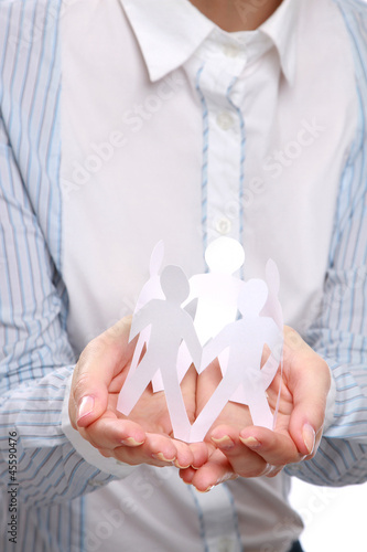 Female hands holding paper people, closeup