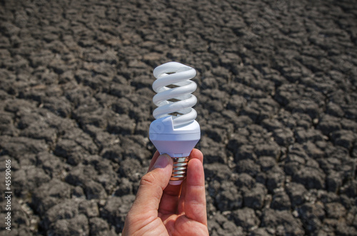 energy saving lamp in hand over drought earth