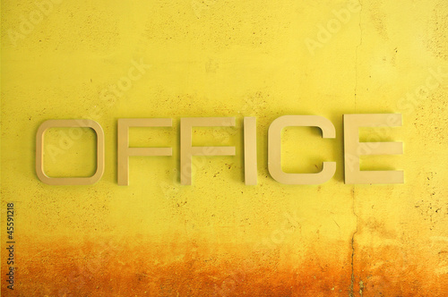 Office text sign on yellow grunge cement wall