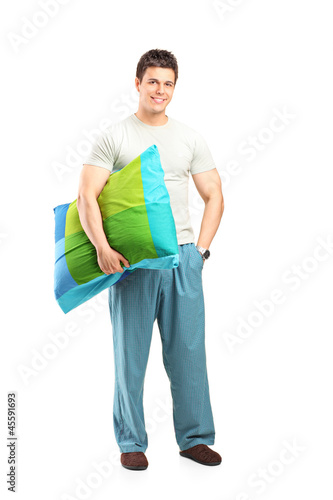 Smiling man in pajamas holding a pillow