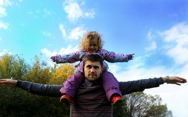 Счастливый ребенок у папы на плечах