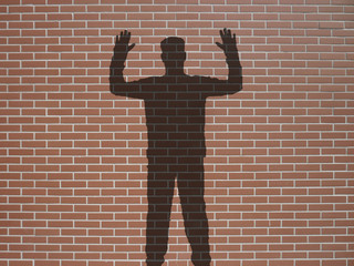 ombre d'homme mains en l'air, sur briques rouges