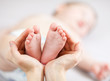 mother hands holding small baby's feet