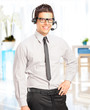 Handsome male customer service operator with headset in his offi