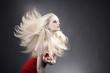 Junge hübsche blonde Frau mit fliegenden Haaren und roten Lippen