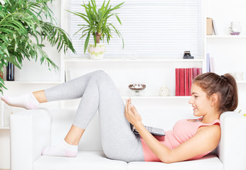 happy woman with laptop lying on the sofa